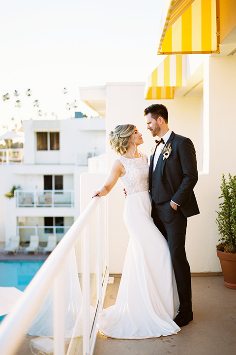 The-Inn-at-Laguna-Beach-bride-and-groom-on-the-balcony-bride-in-a-silk-dress-with-a-boat-neckline-and-hair-up-in-a-bun-and-groom-in-a-slate-blue-suit-with-a-matching-bow-tie