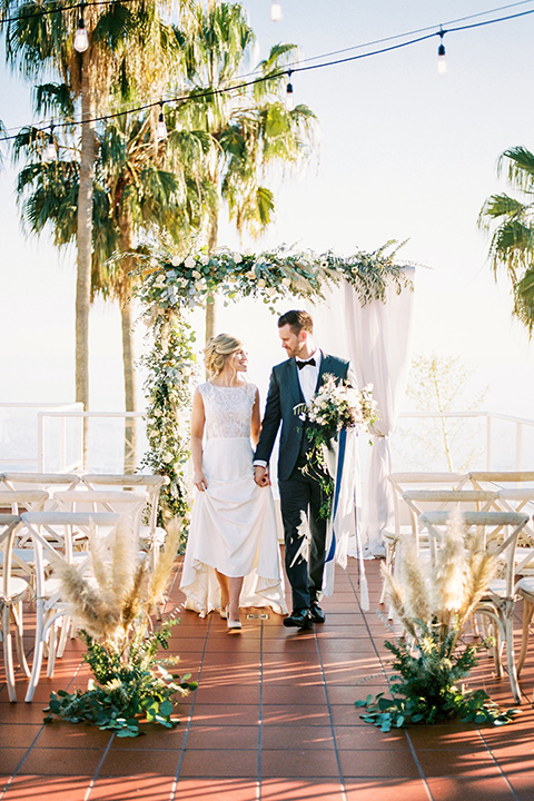 The-Inn-at-Laguna-Beach-bride-and-groom-walking-after-ceremony-bride-in-a-form-fitting-gown-with-a-high-slit-and-high-neckline-groom-in-a-grey-blue-suit-with-a-matching-bow-tie