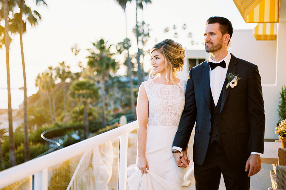 The-Inn-at-Laguna-Beach-bride-and-groom-walking-at-sunset-bride-wearing-a-white-silk-dress-with-a-high-neckline-groom-wearing-a-slate-bue-suit-with-matching-bow-tie