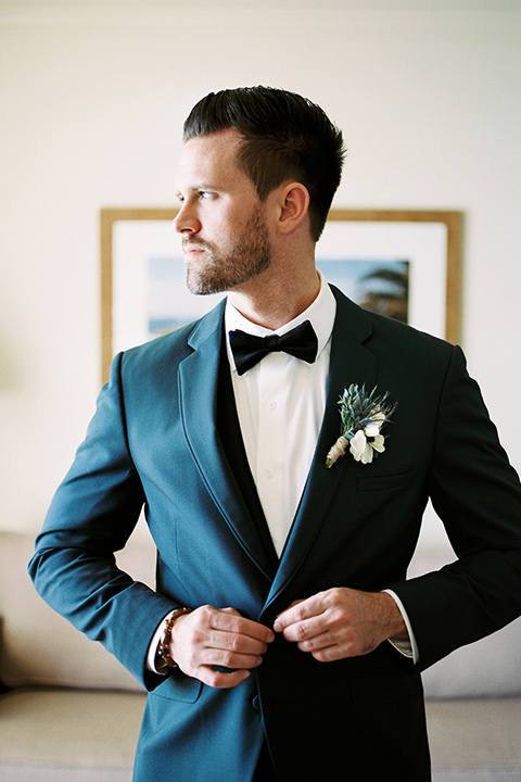 The-Inn-at-Laguna-Beach-groom-buttonging-his-jacket-groom-in-a-grey-blue-suit-with-a-matching-bow-tie