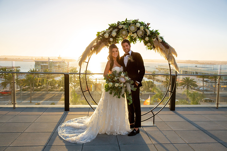 Intercontinental-elopement-shoot-bride-and-groom-at-ceremony-space-groom-in-velvet-tuxedo-with-black-ants-and-a-black-bow-tie-bride-in-a-flowing-gown-with-straps-and-lace