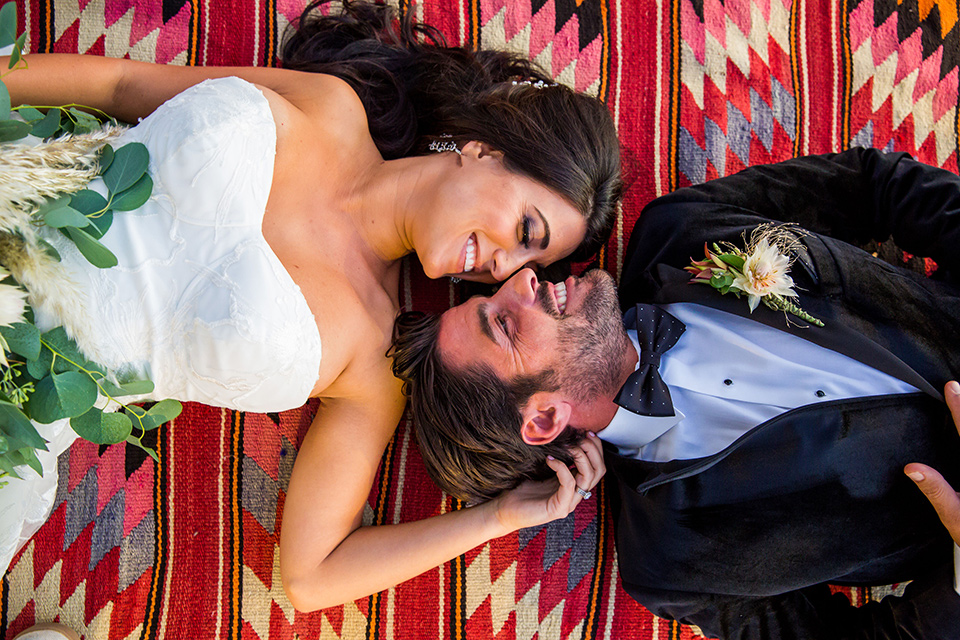 Intercontinental-elopement-shoot-bride-and-groom-on-blanket-groom-in-velvet-tuxedo-with-black-ants-and-a-black-bow-tie-bride-in-a-flowing-gown-with-straps-and-lace