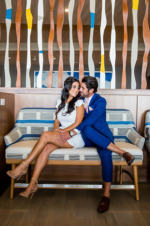 Intercontinental-elopement-shoot-bride-and-groom-on-the-couch-bride-in-a-short-dress-with-straps-groom-in-a-cobalt-blue-suit-with-floral-tie