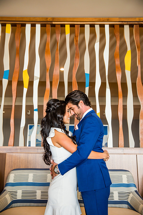 Intercontinental-elopement-shoot-bride-and-groom-touching-heads-bride-in-a-short-dress-with-straps-groom-in-a-royal-blue-suit