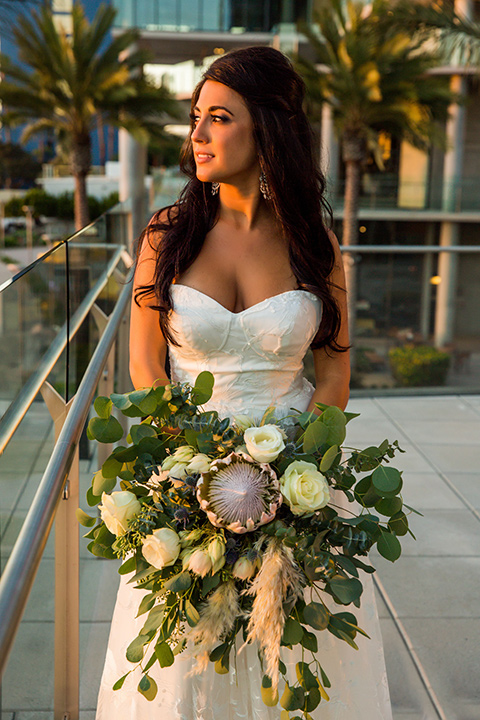 Intercontinental-elopement-shoot-bride-looking-out-on-the-patio-in-a-flowing-lace-gown-with-straps
