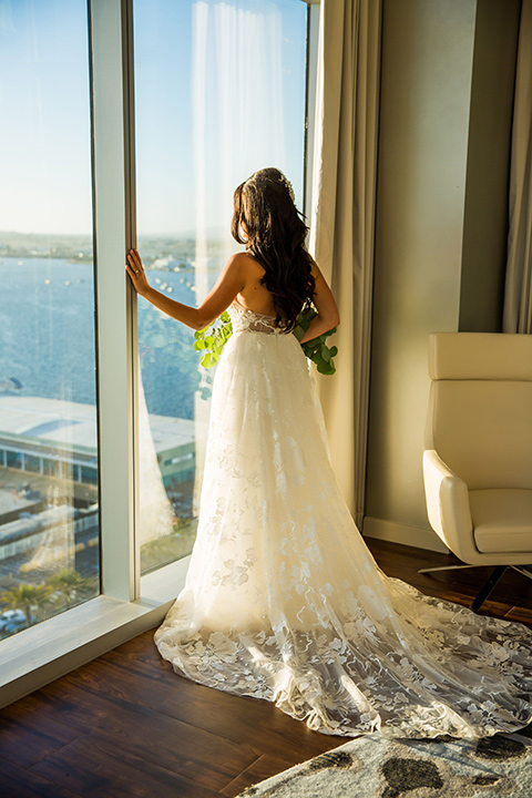 Intercontinental-elopement-shoot-bride-looking-out-the-window-bride-in-a-flowing-white-gown-with-lace