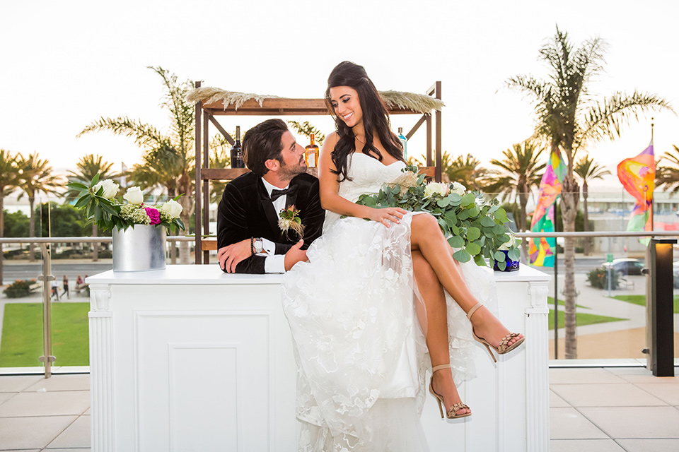 Intercontinental-elopement-shoot-bride-on-bar-groom-behind-the-bar-groom-in-velvet-tuxedo-with-black-ants-and-a-black-bow-tie-bride-in-a-flowing-gown-with-straps-and-lace