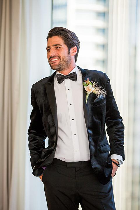 Intercontinental-elopement-shoot-groom-in-black-velvet-by-windows-in-a-velvet-black-tuxedo-and-black-bow-tie