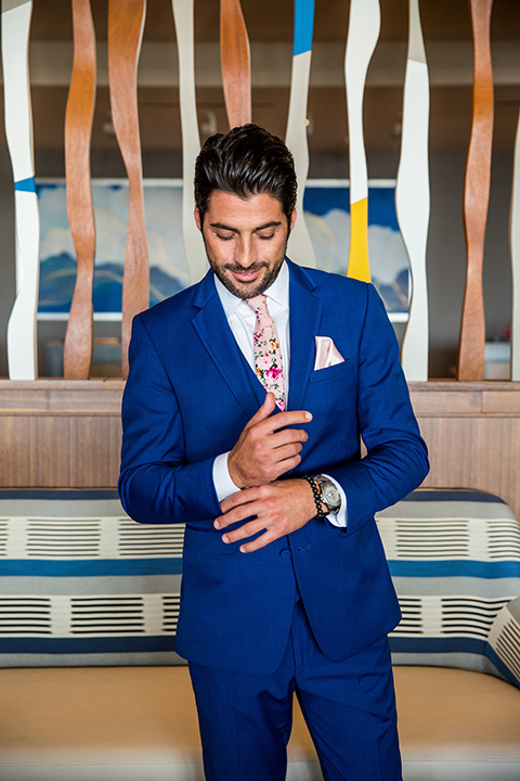 Intercontinental-elopement-shoot-groom-in-blue-fixing-cuff-of=cobalt-blue-suit-with-a-pink-floral-long-tie