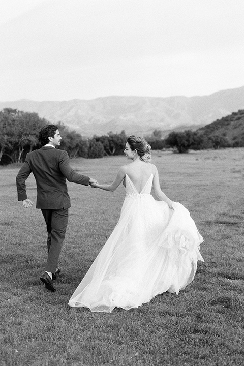 italian-style-wedding-bride-and-groom-black-ad-white-photo-of-them-walking-away-bride-in-a-flowing-gown-with-straps-and-her-hair-up-groom-in-a-grey-tuxedo