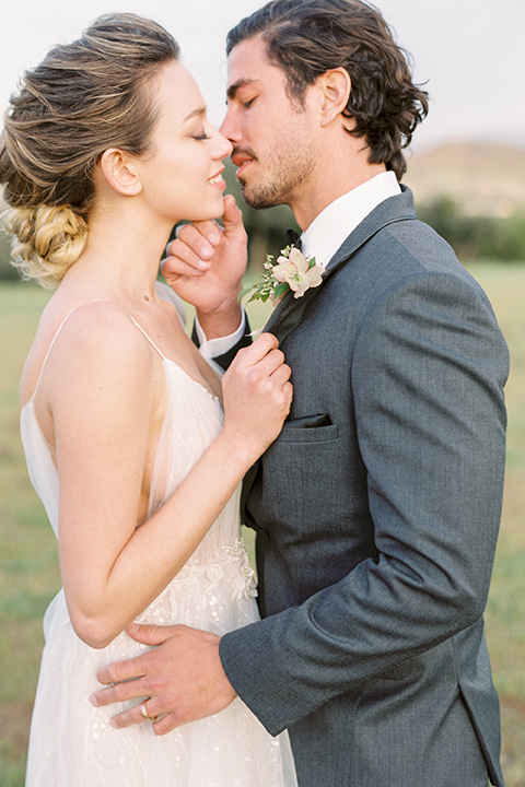 italian-style-wedding-bride-and-groom-close-up-almost-kissing-bride-in-a-flowing-gown-with-straps-and-her-hair-up-groom-in-a-grey-tuxedo