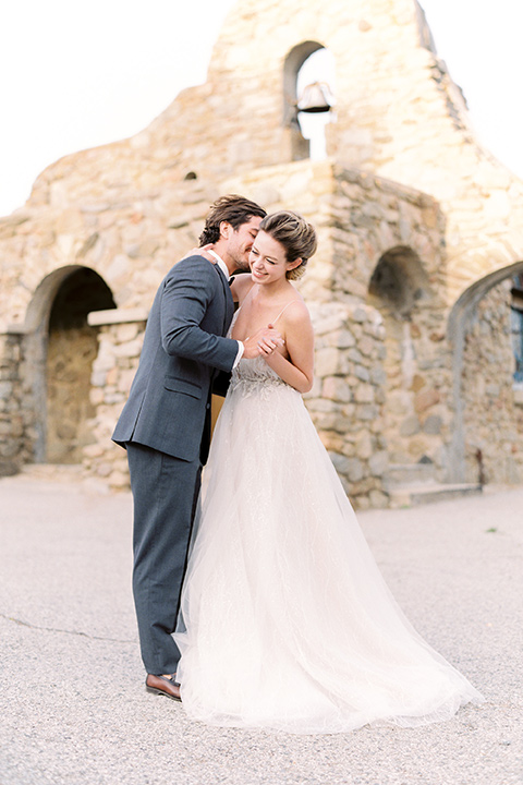 italian-style-wedding-bride-and-groom-dancing--by-stone-wall-bride-in-a-flowing-gown-with-straps-groom-in-a-grey-tuxedo-with-black-bow-tie