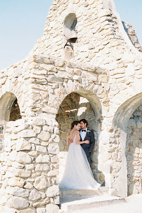italian-style-wedding-bride-and-groom-in-bell-tower-bride-in-a-flowing-gown-with-straps-groom-in-a-grey-tuxedo-with-black-bow-tie