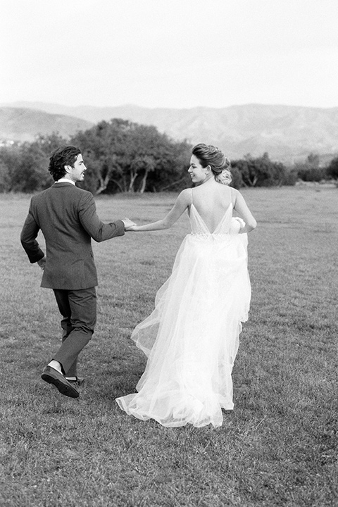 italian-style-wedding-bride-and-groom-walking-away-bride-in-a-flowing-gown-with-straps-groom-in-a-grey-tuxedo-with-black-bow-tie
