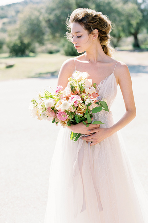 italian-style-wedding-bride-holding-flowers-in-a-flowing-gown-with-straps-and-her-hair-up