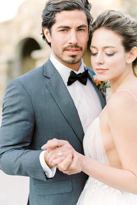 italian-style-wedding-groom-looking-at-camera-holding-bride-close-bride-in-a-flowing-gown-with-straps-and-her-hair-up-groom-in-a-grey-tuxedo
