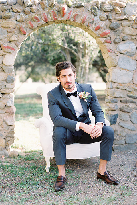italian-style-wedding-groom-sitting-on-chair-in-a-grey-tuxedo-with-black-bow-tie