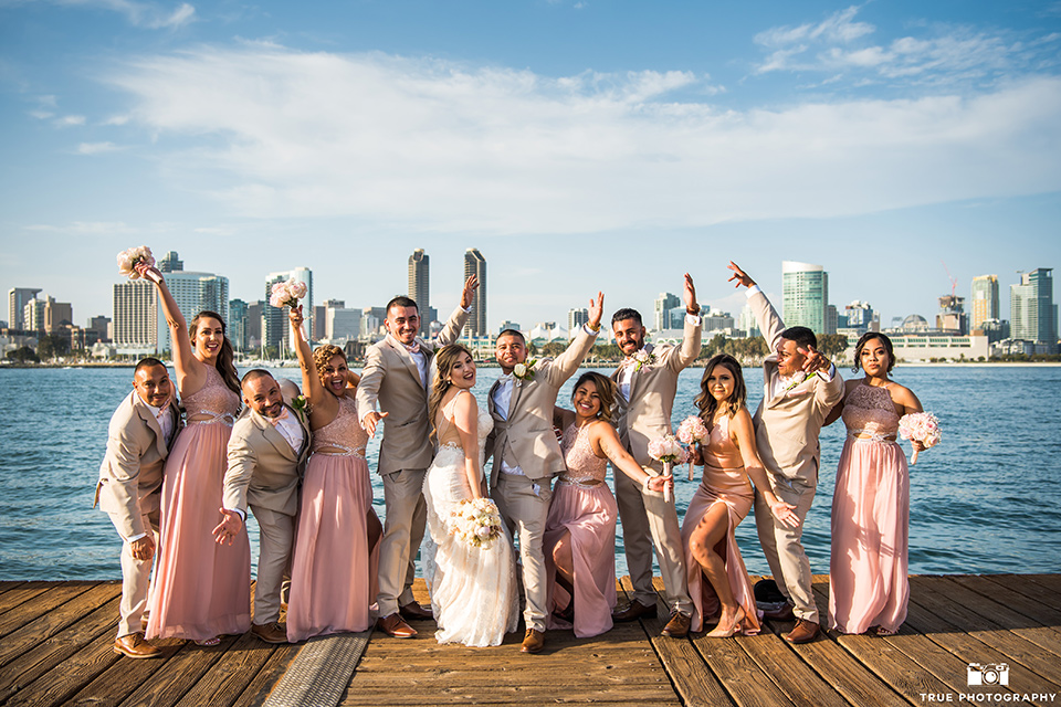 bridal party poses by the water with the bridesmaids wear blush pink long dresses and the groomsmen wearing tan notch lapel suits