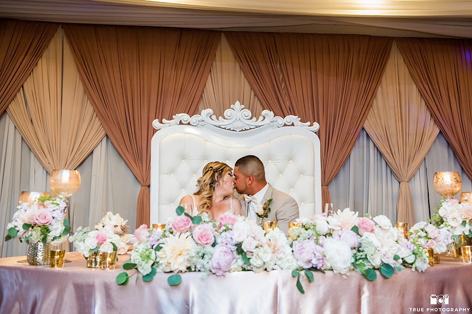 Bride and groom kiss at the sweetheart table during the wedding reception
