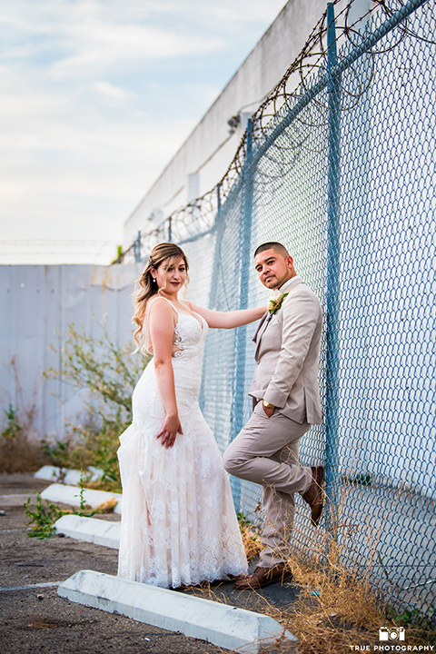 bride and groom pose in front of fence with the bride wearing an ivory lace dress and the groom is wearing a tan suit with a pink bow-tie