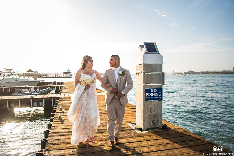 Wedding bride and groom walking on a boardwalk in San Diego