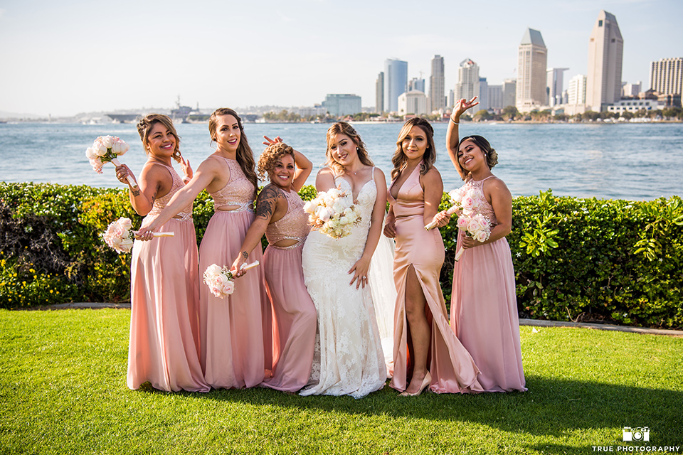 bride and bridesmaids pose in front of san diego skyline