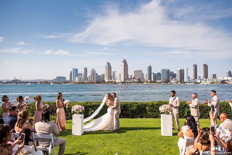 bride and groom kiss during wedding ceremony in front of downtown san diego skyline
