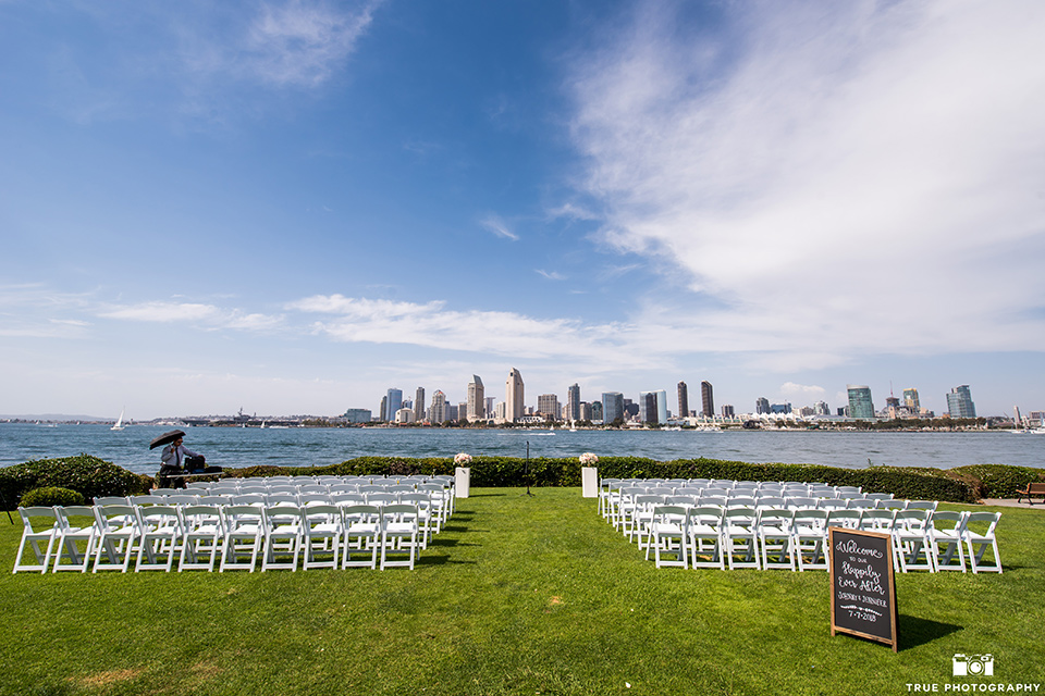 Fiesta Hall wedding ceremony space overlooking the bay with the city scenery in the background with white chairs for guests