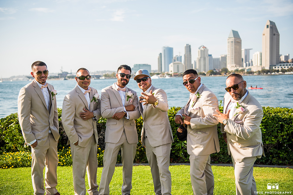 grooms and groomsmen pose in tan notch lapel suits and bow ties