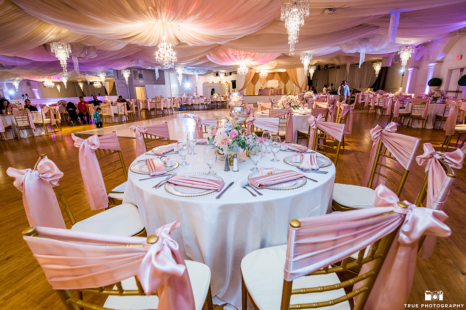 Fiesta Hall wedding reception space with white liners and pink ribbon details and gold flatware