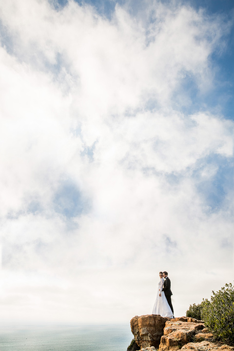bride and groom on a cliff in San Diego with the bride in a lace and tulle gown with long sleeves and high neckline groom in a black tuxedo with black bow tie