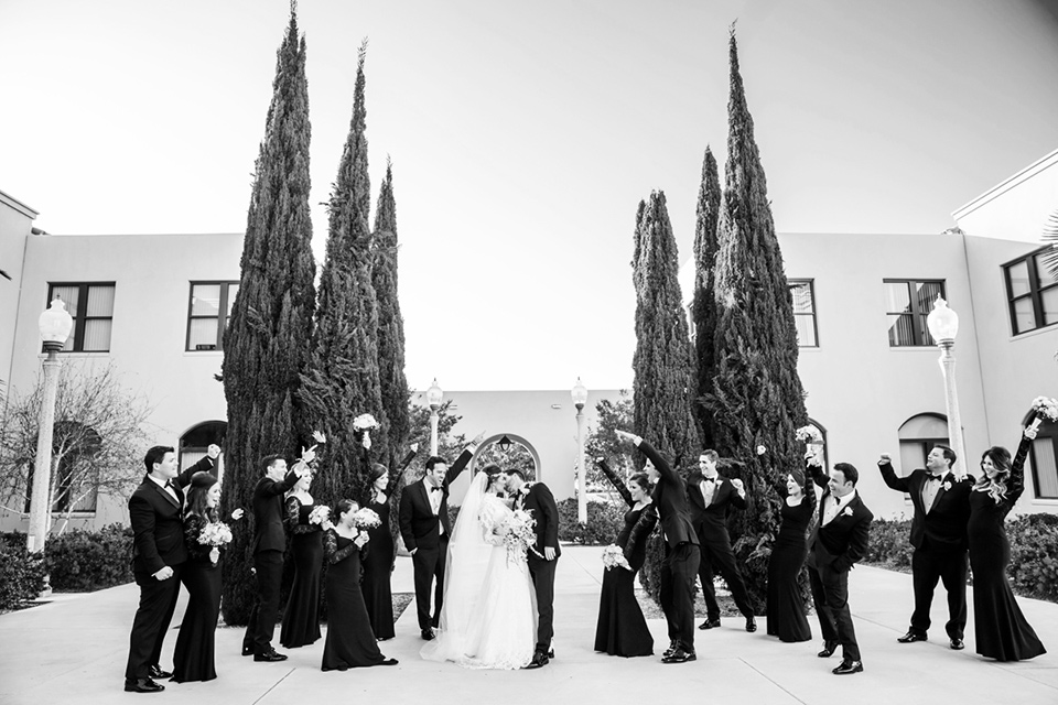 black and white photo of bridal party cheering for couple with bridesmaids in black lace gowns groomsmen in black tuxedos bride in a lace and tulle gown with a high neckline and sleeves groom in a traditional black tuxedo