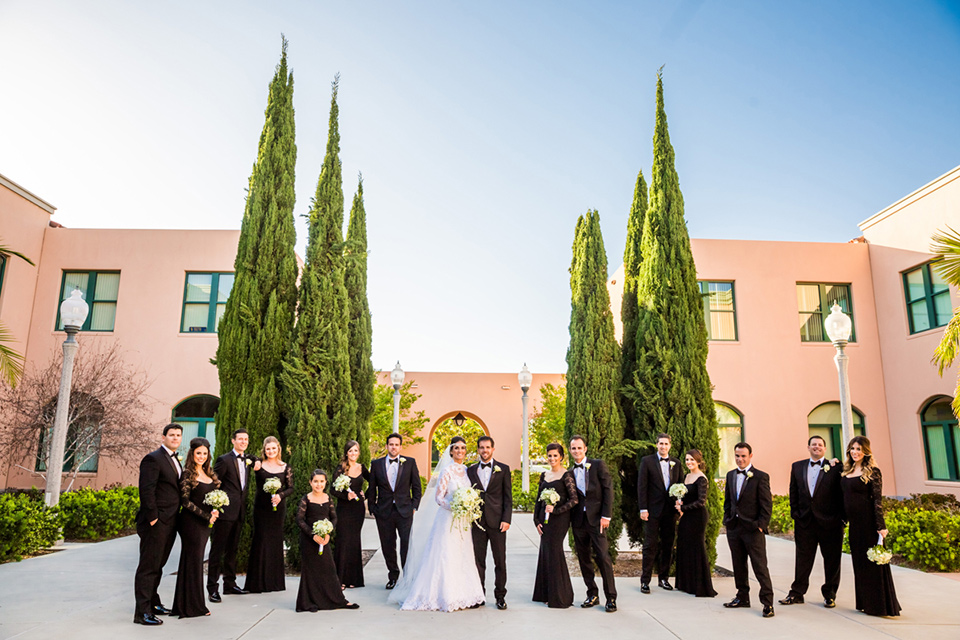 Admiral Kidd Club bridal party standing looking at camera bridesmaids in black lace gowns groomsmen in black tuxedos bride in a lace and tulle gown with a high neckline and sleeves groom in a traditional black tuxedo