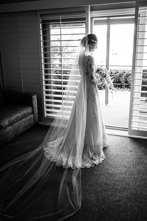 black and white photo of the bride looking out a window in a lace and tulle gown with long sleeves and high neckline groom in a traditional black tuxedo with black bow tie