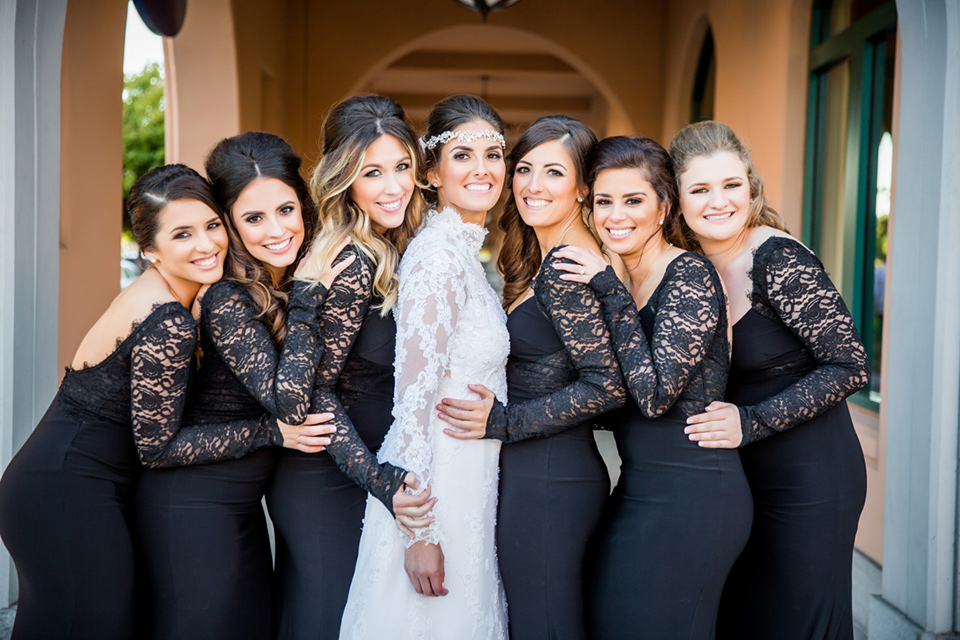 bridesmaids in black lace gowns bride in a lace and tulle gown with a high neckline and sleeves