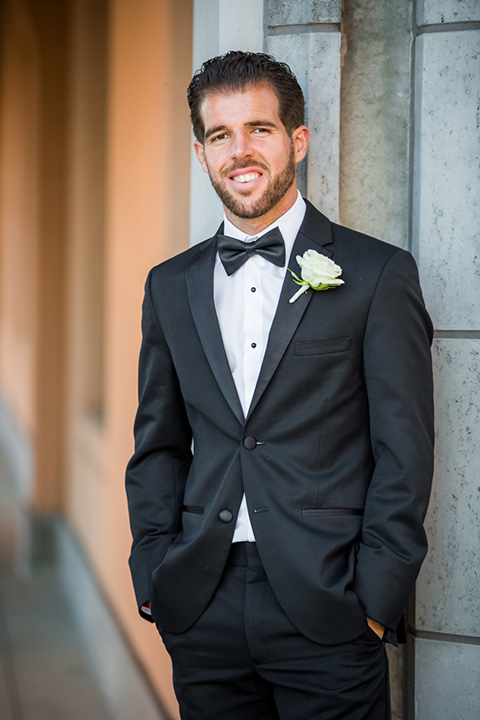 wedding groom in a black tuxedo posing in front of Admiral Kidd Club