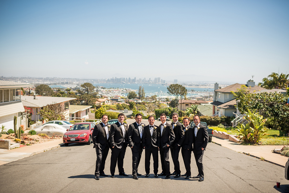 groomsmen  in  black  tuxedos  groom  in  a  traditional  black  tuxedo posing in front of San Diego skyline