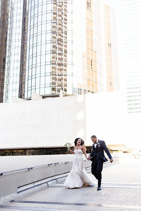 walt-disney-concert-hall-bride-and-groom-running-bride-in-a-mermaid-style-gown-with-a-elbow-length-veil-groom-in-a-navy-shawl-lapel-tuxedo
