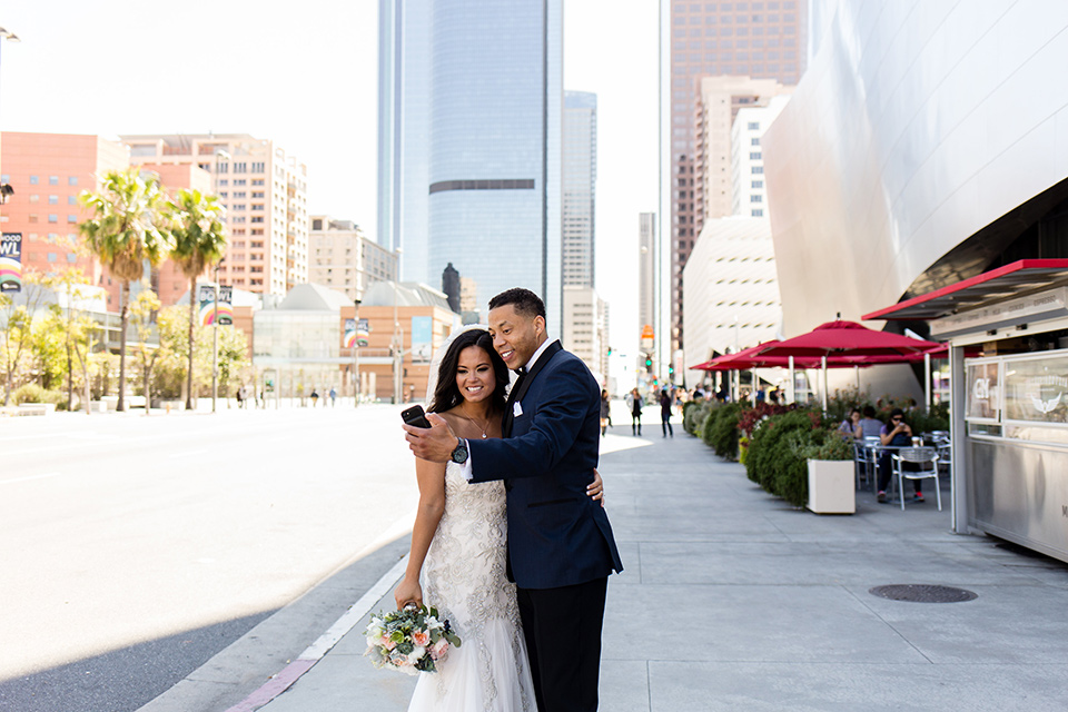 walt-disney-concert-hall-bride-and-groom-taking-a-selfie-bride-in-a-strapless-white-gown-with-a-sweetheart-neckline-groom-in-a-navy-tuxedo