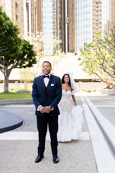 walt-disney-concert-hall-first-look-bride-in-a-mermaid-style-gown-with-a-elbow-length-veil-groom-in-a-navy-shawl-lapel-tuxedo