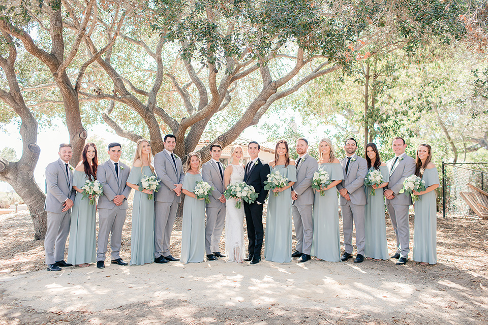 Arroyo-Grande-Wedding-bridal-party-in-a-line-bridesmaids-in-seafoam-light-green-dresses-groomsmen-in-light-grey-suits-bride-in-a-boho-style-gown-with-a-keyhole-back-and-high-neckline-and-fringe-white-the-groom-wore-a-traditional-black-tuxedo-and-black-long-tie