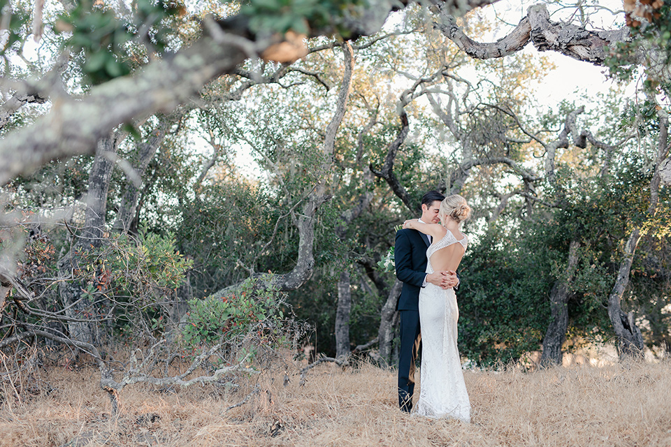Arroyo-Grande-Wedding-bride-and-groom-hugging-under-tree-bride-in-a-boho-style-gown-with-a-keyhole-back-and-high-neckline-and-fringe-white-the-groom-wore-a-traditional-black-tuxedo-and-black-long-tie
