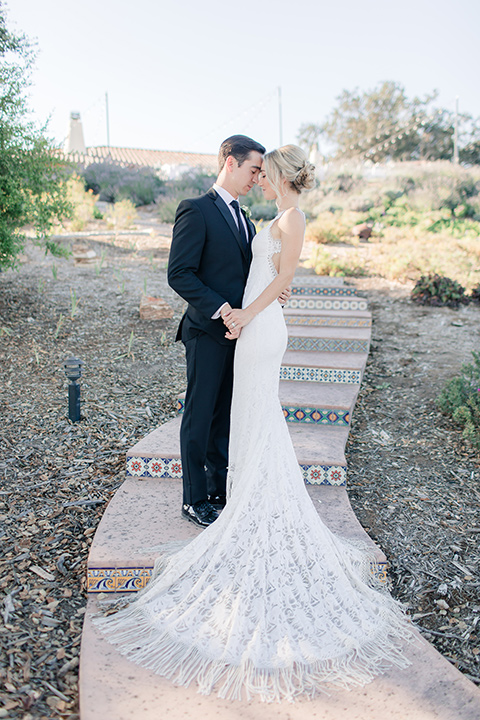 Arroyo-Grande-Wedding-bride-and-groom-on-steps-touching-heads-bride-in-a-boho-style-gown-with-a-keyhole-back-and-high-neckline-and-fringe-white-the-groom-wore-a-traditional-black-tuxedo-and-black-long-tie