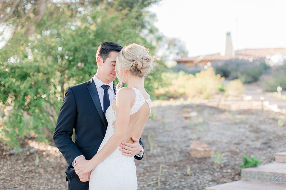 Arroyo-Grande-Wedding-bride-and-groom-standing-close-together-on-steps-bride-in-a-boho-style-gown-with-a-keyhole-back-and-high-neckline-and-fringe-white-the-groom-wore-a-traditional-black-tuxedo-and-black-long-tie