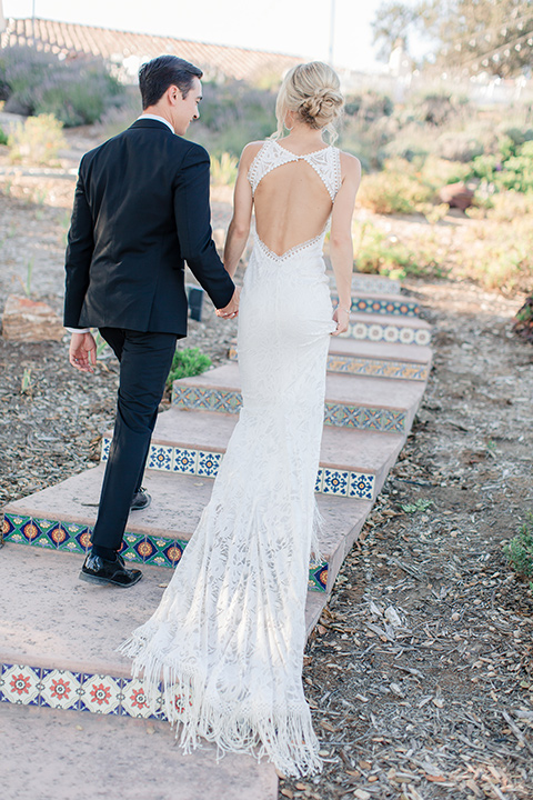 Arroyo-Grande-Wedding-bride-and-groom-walking-away-bride-in-a-boho-style-gown-with-a-keyhole-back-and-high-neckline-and-fringe-white-the-groom-wore-a-traditional-black-tuxedo-and-black-long-tie