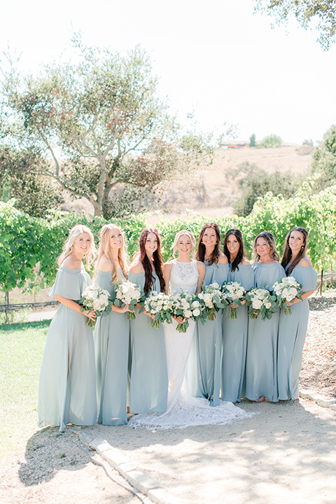 Arroyo-Grande-Wedding-bridesmaids-bride-in-a-boho-style-gown-with-a-keyhole-back-and-high-neckline-and-fringe-the-bridesmaids-wore-light-sage-off-the-shoulder-dresses