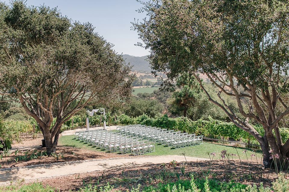 Arroyo-Grande-Wedding-ceremony-space-in-a-grass-area-with-simple-wooden-chairs-and-archway-surrounded-by-trees