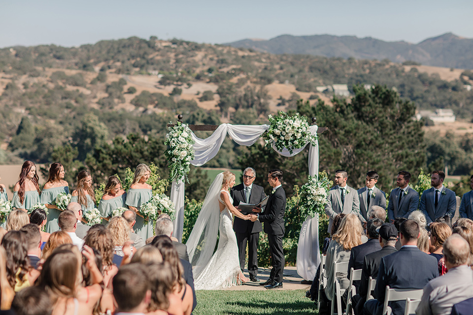 Arroyo-Grande-Wedding-ceremony-bride-in-a-boho-style-gown-with-a-keyhole-back-and-high-neckline-and-fringe-white-the-groom-wore-a-traditional-black-tuxedo-and-black-long-tie