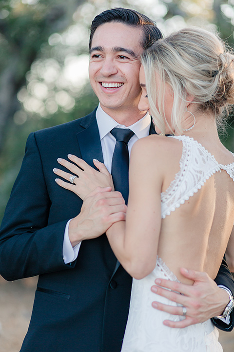 Arroyo-Grande-Wedding-couple-holding-each-other-bride-in-a-boho-style-gown-with-a-keyhole-back-and-high-neckline-and-fringe-white-the-groom-wore-a-traditional-black-tuxedo-and-black-long-tie