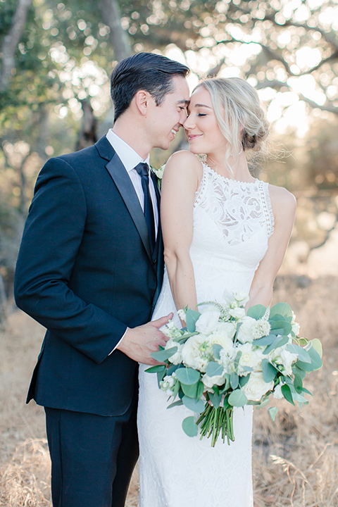 Arroyo-Grande-Wedding-couple-touching-heads-bride-in-a-boho-style-gown-with-a-keyhole-back-and-high-neckline-and-fringe-white-the-groom-wore-a-traditional-black-tuxedo-and-black-long-tie